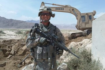 U.S Army solider Brian Ross holding a rifle at a construction site in Afghanistan with a backhoe in the background