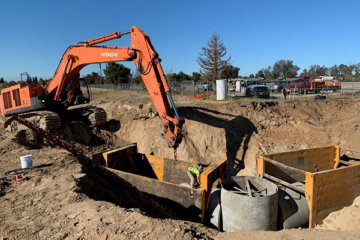 A backhoe lowers a piece of large pipe into a worksite