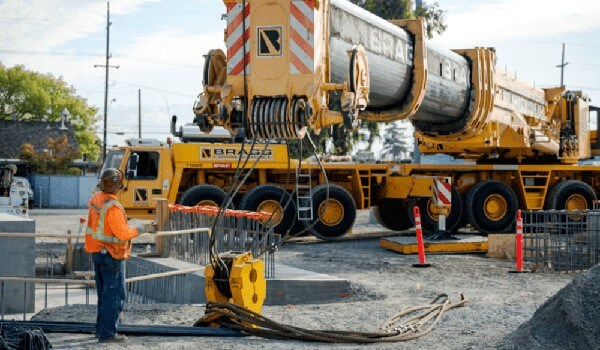 crews installing electrification infrastructure for Caltrain