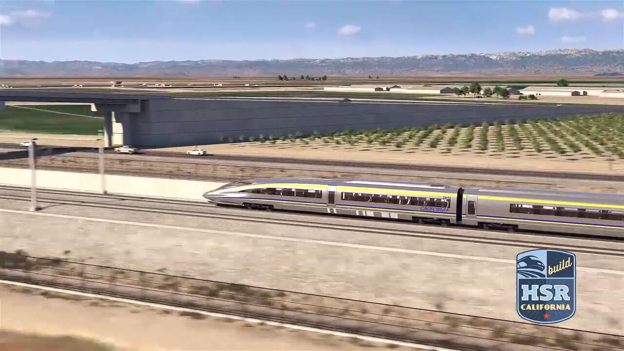 Still from video showing a simulation of high-speed rail cars approaching a grade separation.