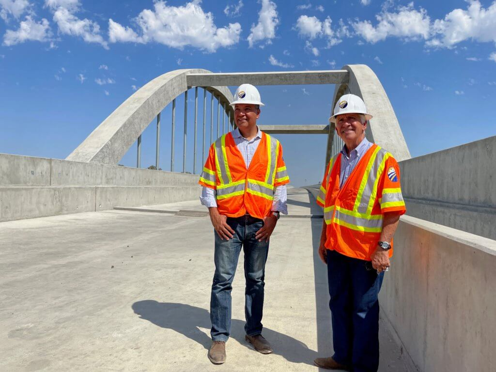California Senator Alex Padilla and Congressman Jim Costa stand on the award winning San Joaquin River Viaduct with the singature arches and a beautiful blue and cloud flecked sky behind them.