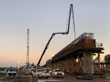 Viaduct structure under construction at dusk with pickup trucks parked on left side and cement truck piping cement to top of structure