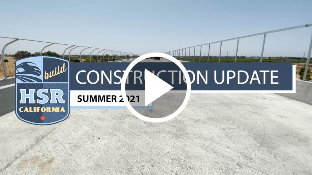 A still of the video, which reads Construction Update Summer 2021, shwoing a complete concrete road deck over tracks, and a super imposed play button, encouraging seeing readers to click the image to be directed to the video on YouTube.
