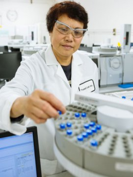 A Torrent Laboratory chemist conducts stands in front of machinery to test for dioxin compounds.